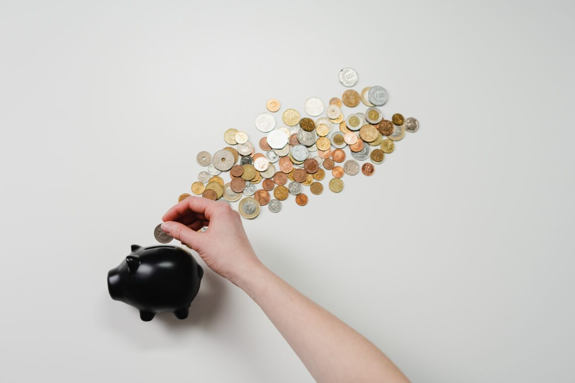 woman saving money into a black piggy bank
