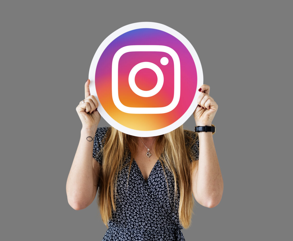 woman holding the instagram sign covering her face